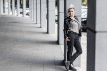 Portrait of punk woman leaning against column — Stock Photo