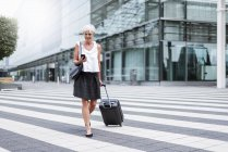 Smiling senior woman with baggage on the move with cell phone — Stock Photo
