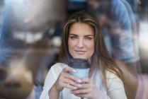 Retrato de sorrindo jovem mulher atrás do vidro da janela com café takeaway — Fotografia de Stock