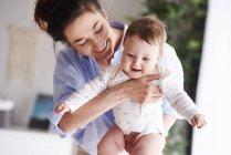 Feliz madre llevando a su bebé en casa - foto de stock