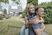 Улыбающаяся зрелая пара обнимается в саду дома — стоковое фото