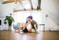 Ласковая пара, сидящая на полу в современном доме — стоковое фото