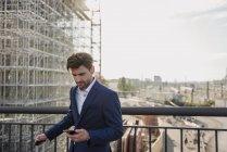 Empresário em pé na ponte da cidade usando telefone celular — Fotografia de Stock