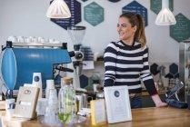 Lächelnde junge Frau hinter der Theke eines Cafés — Stockfoto