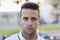 Retrato de jovem sério no fundo borrado da cidade — Fotografia de Stock