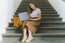 Woman sitting on a staircase using laptop — Stock Photo