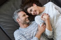 Happy couple lying on couch at home — Stock Photo