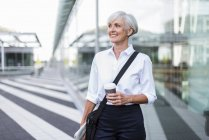 Smiling senior businesswoman in city on the go with takeaway coffee — Stock Photo