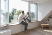 Mature couple with cell phone sitting at window in empty room — Stock Photo