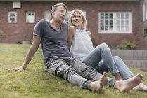 Молодая пара, сидящая в саду дома — стоковое фото