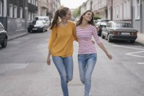 Two cheerful girlfriends having fun in city, walking arm in arm — Stock Photo