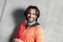 Portrait d'athlète souriant au mur de béton — Photo de stock