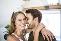 Happy couple at home with woman wearing tiara — Stock Photo