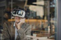 Homme d'affaires mûr s'asseyant dans le café, regardant par des glaces de Vr — Photo de stock