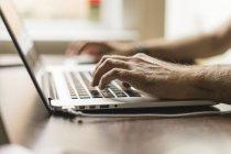 La mano del hombre en el teclado del portátil, vista parcial - foto de stock