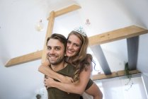 Retrato de casal feliz em casa com mulher vestindo tiara — Fotografia de Stock