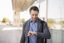 Empresário sorridente com saco de laptop verificando o tempo — Fotografia de Stock