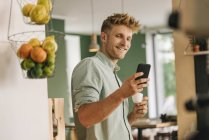 Молодой владелец бизнеса пьет кофе, проверяет смартфон — стоковое фото