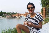 Улыбающаяся молодая женщина в солнечных очках на берегу реки с помощью мобильного телефона — стоковое фото