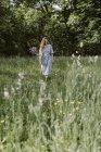 Италия, Мбато, молодая женщина, вырывающая цветы и травы в поле — стоковое фото