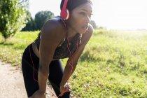 Atleta novo na natureza, música de escuta com auscultadores, preparando-se para o treinamento — Fotografia de Stock