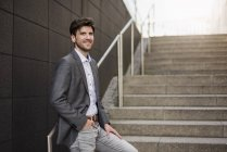 Smiling young businessman standing on stairs — Stock Photo