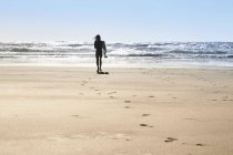 Portugal, Algarve, silhouette of man walking on beach with surfboard — Stock Photo