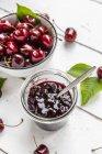 Глек з вишневої Повидла і вишні на білій деревині — стокове фото