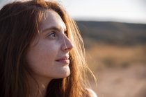 Lächelnde junge Frau mit Sommersprossen, die wegschaut — Stockfoto