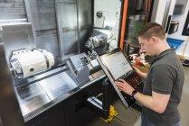 Mann bedient Maschine in Fabrik — Stockfoto
