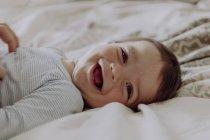 Счастливый ребенок, лежащий на кровати и смеющийся — стоковое фото