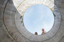Два альтернативных друга смотрят сквозь дыру — стоковое фото