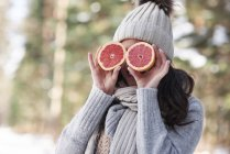 Laughing young woman wearing knitwear covering her eyes with halves of grapefruit — Stock Photo