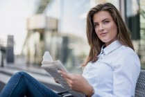 Portrait of smiling young businesswoman sitting on bench with newspaper — Stock Photo