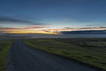 UK, Scotland, Caithness, Duncansby Head, rural road at sunset — Stock Photo