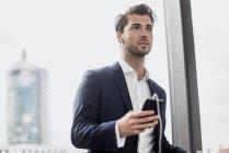 Uomo d'affari alla finestra con cellulare e auricolari — Foto stock