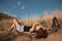 Jeune femme couchée dans le paysage rural — Photo de stock