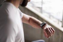 Спортсмен проверяет время на умных часах — стоковое фото