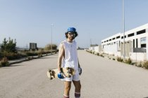 Retrato do homem Sportive no branco e no azul com o skate na estrada pavimentada cinzenta vazia — Fotografia de Stock