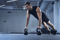 Man doing pushups on kettlebells at gym — Stock Photo