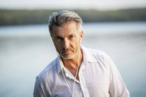 Portrait of mature man with earphones at lake — стоковое фото