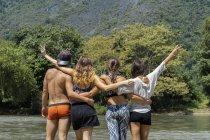 Лаос, группа друзей, стоящих у реки, обнимающихся с вешалками — стоковое фото
