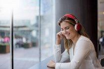 Счастливая молодая женщина слушает музыку в наушниках — стоковое фото