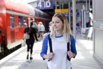 Portrait of blond woman with backpack on platform — Stock Photo
