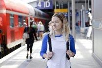 Retrato de mulher loira com mochila na plataforma — Fotografia de Stock