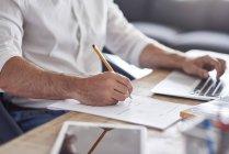La mano de un empresario llena un contrato - foto de stock
