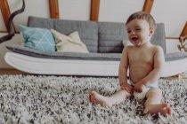 Feliz bebé jugando en la alfombra en casa - foto de stock