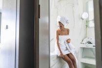 Mulher envolto em toalha, sentado na borda da banheira — Fotografia de Stock
