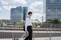 Бизнесмен с чемоданом на мосту проверяет время — стоковое фото