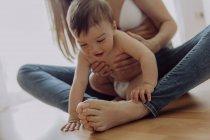 Mutter kuschelt und spielt mit Baby-Sohn auf dem Boden — Stockfoto